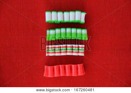 Horizontal image of simple red background with four colorful pieces of  old-fashioned ribbon candy, a favorite at Christmastime.