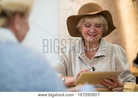 Senior woman with tablet smiling. Elderly lady looking at gadget. Use the best media portal.