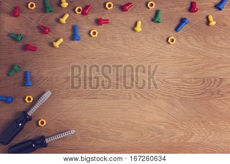 Kids Toys Background Frame Boarder with colorful nuts, bolts and two screwdrivers on wooden table. Copy space for text. Top view. Flat lay.
