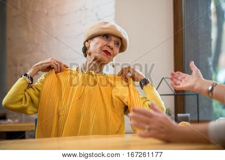 Senior woman holding clothes. Old lady indoors. Bright colors suit me.