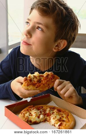 teen boy with pizza slice in the restaurant close up photo thinking disracted