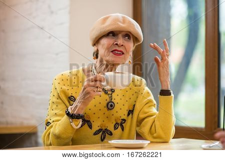 Senior lady drinking coffee. Old woman at the table. Talk with confidence.