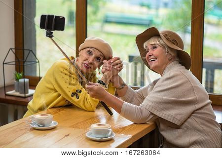 Women taking selfie in cafe. Senior ladies shaking hands. Years pass but friendship remains.