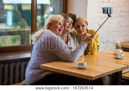 Selfie of ladies in cafe. Senior women smiling. Years pass but friends remain.