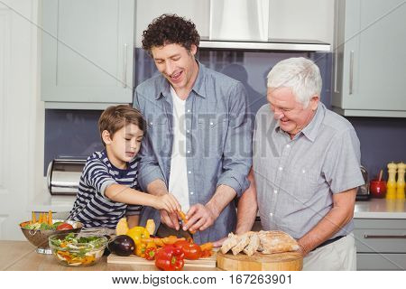 Happy family preparing food in kitchen at home