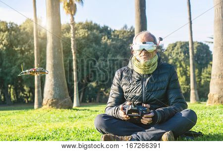 Senior man having fun with new technologies of flying drones wearing virtual reality glasses - Adult piloting his racer drone built by himself with remote control - First person view