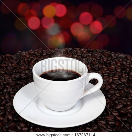 Black coffee and smoke in white cup over coffee beans with blurry night light background.