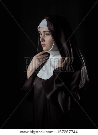 portrait of the young beautiful nun. Low key lighting. On black.