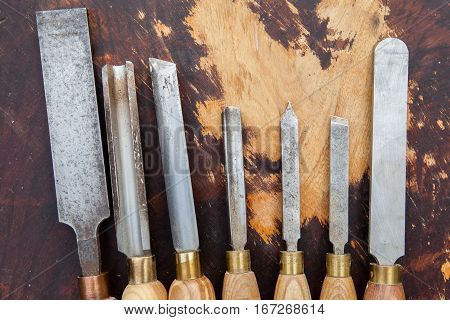 Old used wood lathe chisels selection on the dark wooden table selective focus