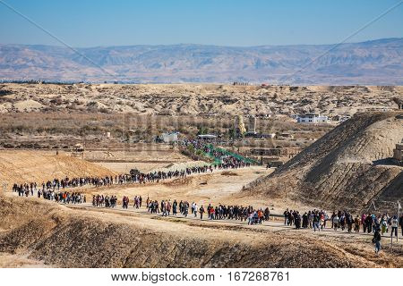 THE BORDER WITH JORDAN, ISRAEL - JANUARY 18, 2008: Tourists and pilgrims and walk through desert after visiting the Jordan River.  The Day of the Christian feast of the Epiphany