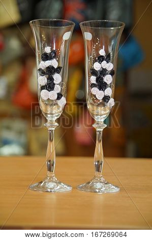 beautiful wedding decor: two glasses of thin glass decorated with garlands of flowers from polymer clay