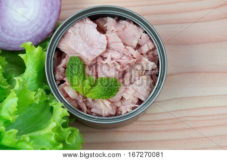 canned tuna on wood table / Canned albacore pink meat tuna packed in water
