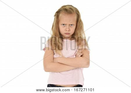 cute and sweet young schoolgirl with blond hair and folded arms looking angry and upset in frustrated and unhappy face expression in child education and emotions concept isolated white background