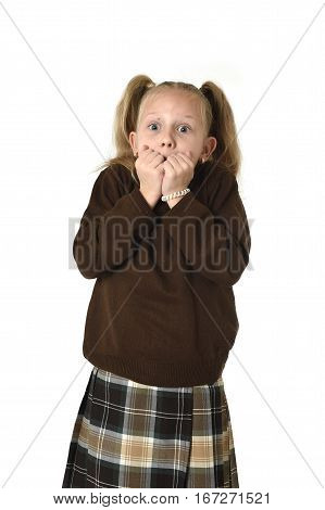 young beautiful and sweet schoolgirl in pigtails and school uniform looking amazed shocked and surprised in female child scared face expression isolated on white background