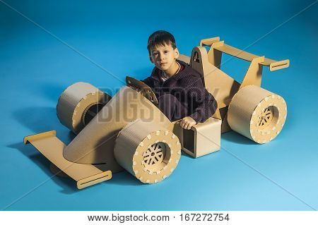 photo of young racer on a cardboar racing car on blue background