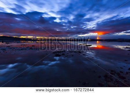 Flame On Horizon Of Night Cloudscape Scene Over Water Surface