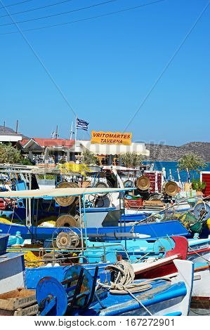 ELOUNDA, CRETE - SEPTEMBER 17, 2016 - Traditional Greek fishing boats moored in the harbour with a taverna to the rear Elounda Crete Greece Europe, September 17, 2016.