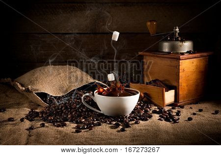 Coffee Art Composition: Scattered Roasted Beans From A Bag, Coffee Grinder With Ground Coffee And A