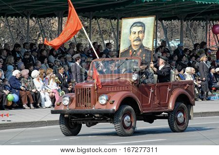 Tyumen, Russia - May 9. 2009: Parade of Victory Day in Tyumen. Members of KPRF with Stalin portrait on SUV of WW2 times on parade