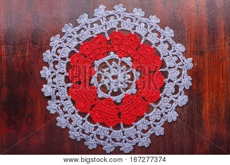 The table knitted napkin of handwork lies on a table from mahogany. The napkin has a pattern from red hearts. Top view.