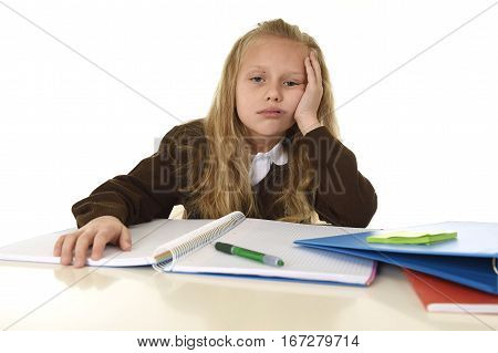 sweet little schoolgirl sad and tired looking depressed suffering stress overwhelmed by load of homework and schoolwork on desk with notepad and pen in school child performance concept