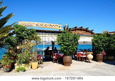 ELOUNDA, CRETE - SEPTEMBER 17, 2016 - Olondi taverna along the waterfront with views across the bay Elounda Crete Greece Europe, September 17, 2016.