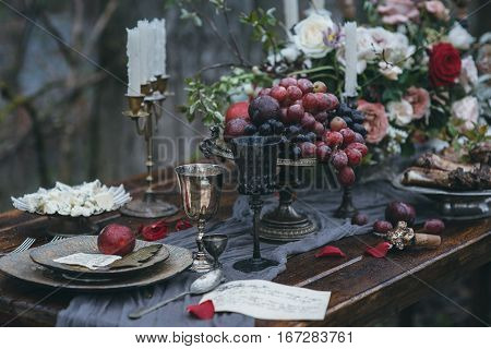 Wedding decoration on nature. Table with meat, flowers and candles