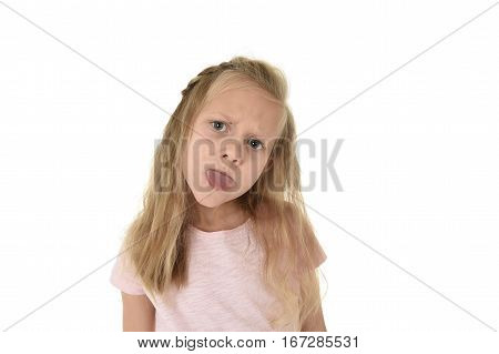 little sweet schoolgirl with pigtails playful and naughty taking tongue out mocking isolated on white background