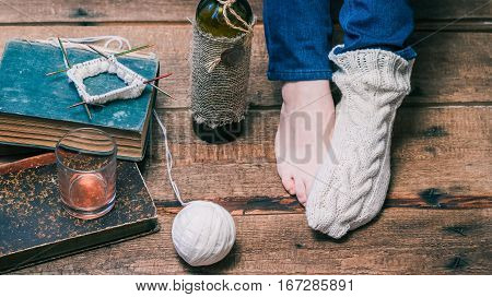 Feet of person wearing one winter sock, knitting the other one and drinking wine