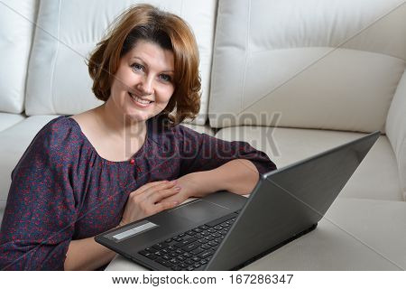 Middle-aged woman working at a computer at home