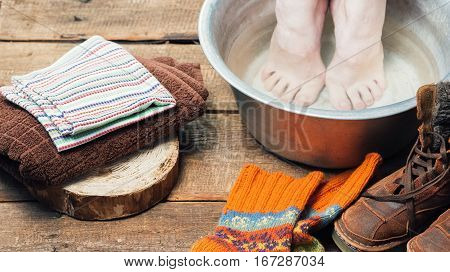 Footbath closeup. Bare foot in basin with warm water,  towels, boots and wool socks on the floor