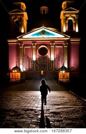 a child runs into the church and illuminated by a beam of light