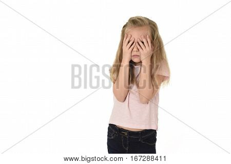 sweet young little schoolgirl covering her face with her hands crying sad victim of bullying at school isolated on white background