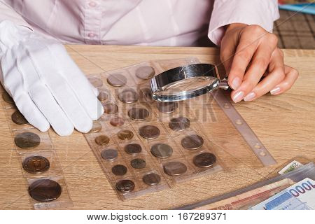 Woman's Hands With Magnifying Glass And A Collection Of Coins