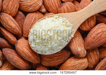 almond flour in wooden spoon on almond background