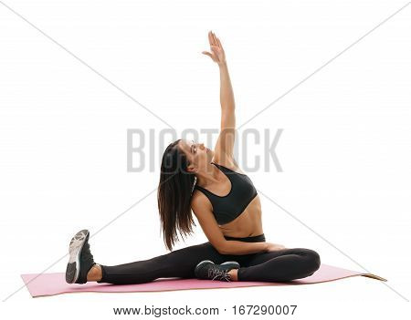 Sporty young brunette in black top and leggings exercing sitting on a rug bending left studio shot
