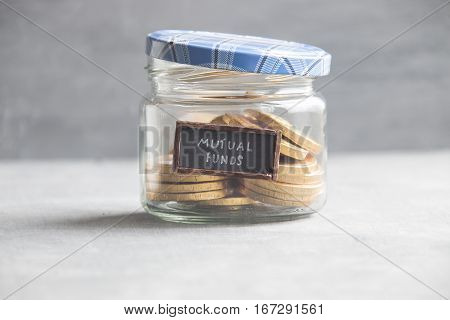 writing MUTUAL FUNDS and gold coins in a glass jar