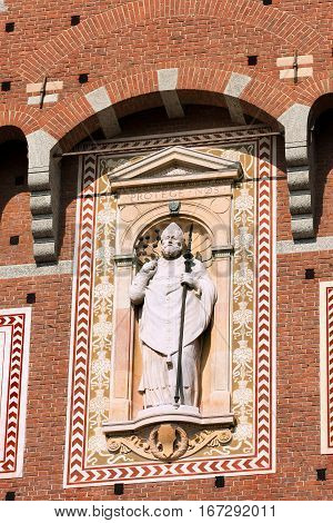 Statue of Sant'Ambrogio (Saint Ambrose) patron of the city of Milano (Milan). Detail of the clock tower of the Sforza Castle XV century (Castello Sforzesco). Lombardy Italy