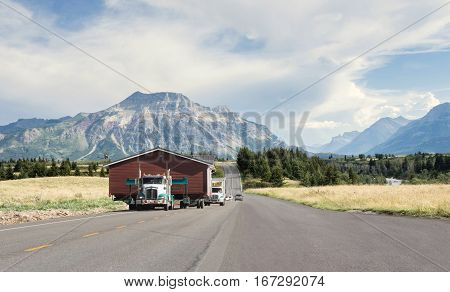 horizontal image of a big transport truck moving a large home along a narrow highway with mountains looming in the background in the summer time.
