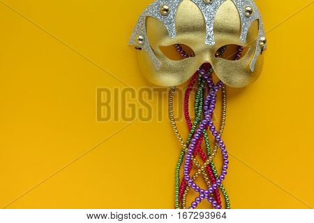 Maris gras mask and beads on yellow background with copy space. Top view