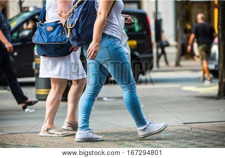 London, UK - August 24, 2016:   Feet of pedestrians walking on the crosswalk in Oxford street, London. Modern life, travel and shopping concept