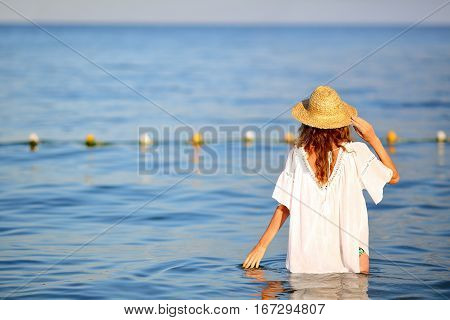 Woman In Straw Hat In Sea Water On The Beach Back To Us