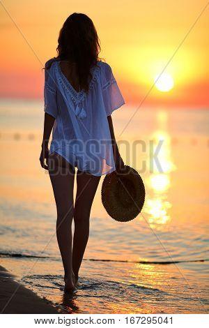 Slim Woman Walking On The Beach At Sunset