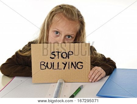 young beautiful schoolgirl scared in stress holding paper with text stop bullying written looking desperate asking for help sitting at school desk alone in victim children bullied and abuse concept poster