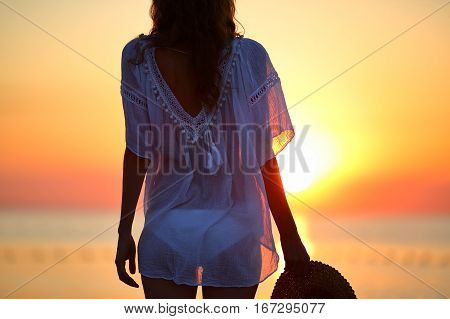 Woman On The Beach At Sunset. Summer Vacations Concept