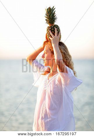 Woman In White Tunic With Pineapple On A Background Of The Sea