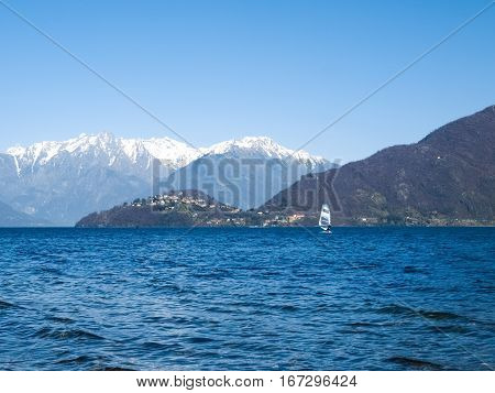 Pianello del Lario Como - Italy: Windsurfer sailing on the lake and in the background you can see the peninsula of Piona and mountains