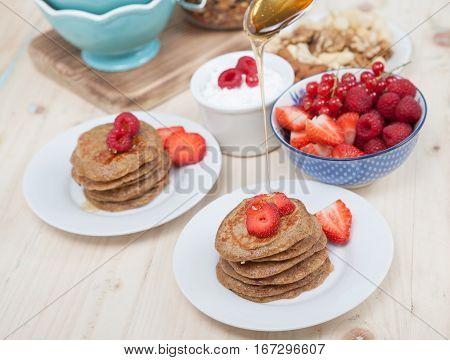 Breakfast: paleo style grain free banana almond pancakes coconut yogurt with berries selective focus