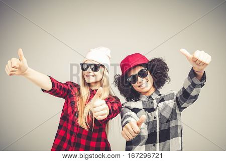 Studio lifestyle portrait of two best friends hipster girls wearing stylish bright outfits, going crazy and having great time together. Isolated on white background.