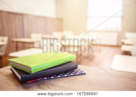 School teacher's desk with stack of books